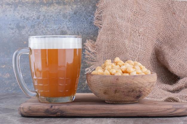 Verre de bière et bol de petits pois sur planche de bois. photo de haute qualité