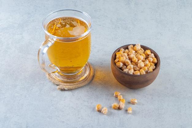 Verre à bière et bol de pois chiches, sur la surface en marbre.