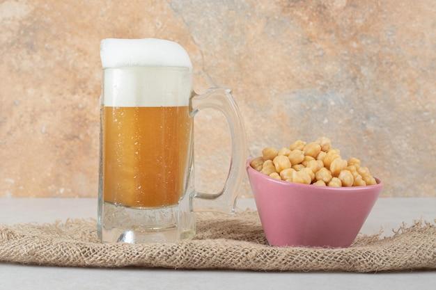 Verre de bière avec bol de pois sur toile de jute