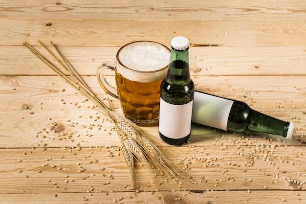 Verre de bière avec des bouteilles et des épis de blé sur une planche de bois