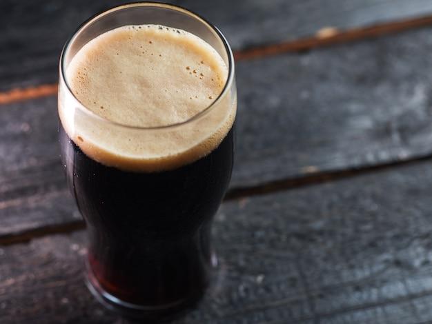 Un verre de bière brune artisanale sur une table en bois dans un pub avec fond