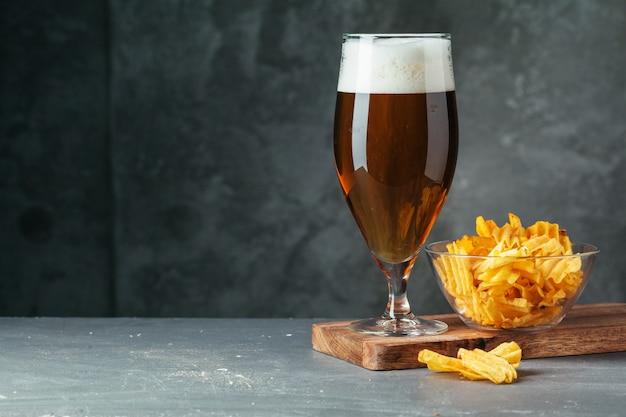 Verre de bière brune avec bol de collations de bière se bouchent
