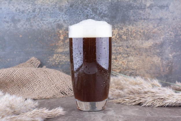 Verre de bière brune avec des épis de blé sur une table en marbre. photo de haute qualité