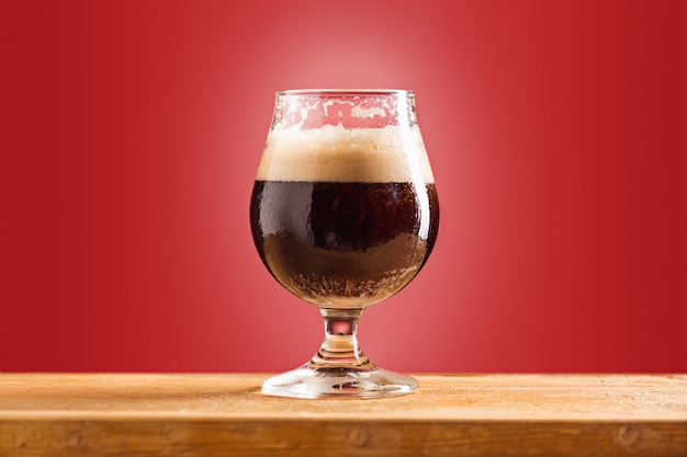 Verre de bière brune mousseuse froide sur une vieille table en bois