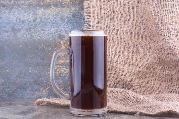 Verre de bière brune sur table en marbre. photo de haute qualité
