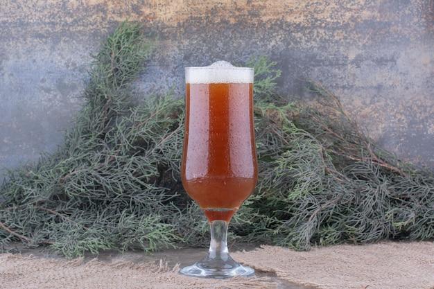 Verre de bière brune sur toile de jute avec branche de pin. photo de haute qualité
