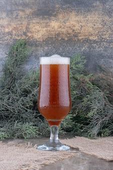 Verre de bière brune sur toile de jute avec branche de pin