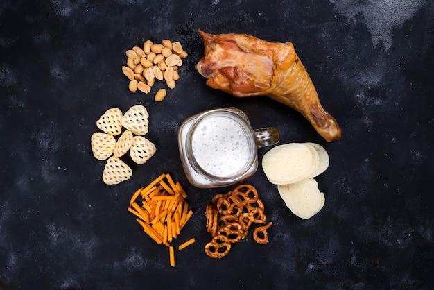 Verre de bière et collations et cuisses de poulet fumées