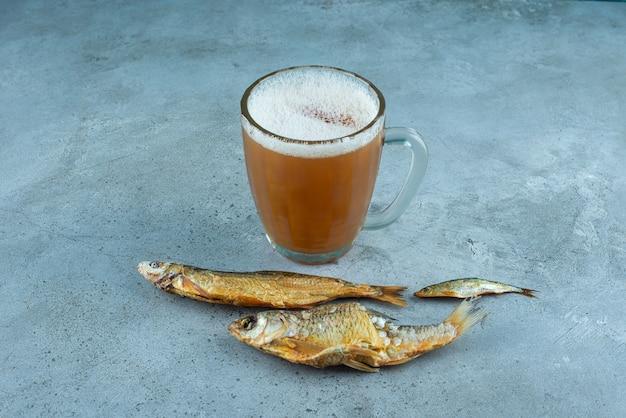 Un verre de bière à côté de poissons, sur la table bleue.