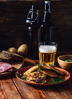 Verre de bière avec crêpes de pommes de terre et quelques collations