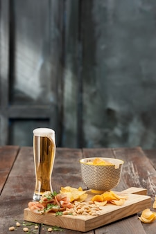 Le verre de bière et de croustilles, pistaches isolées sur fond blanc