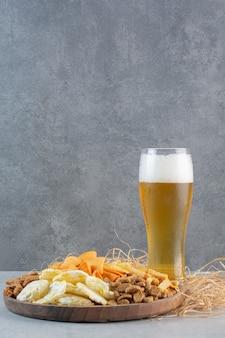 Un verre de bière avec du blé et des croustilles sur du foin.