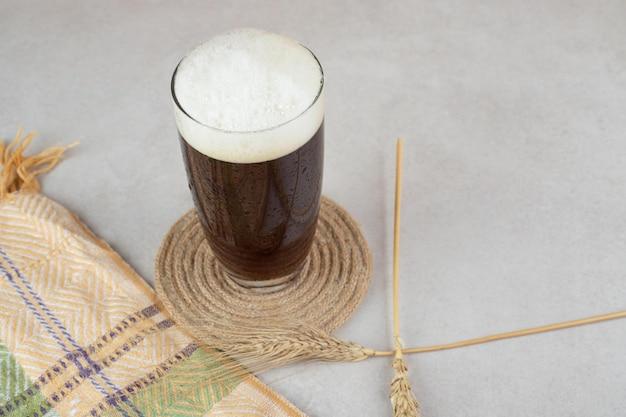 Verre de bière avec du blé sur la surface de la pierre
