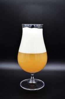 Verre de bière sur fond noir, verre de bière, récipient avec liquide trouble jaune