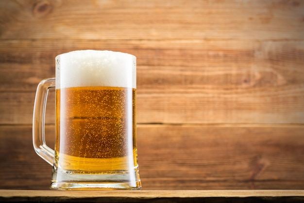 Verre avec bière et frites sur le mur en bois.
