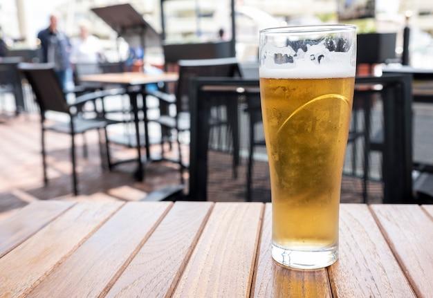 Verre de bière froide avec de la mousse sur une table en bois