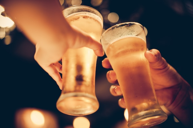 Un verre de bière froide s'agite avec un magnifique bokeh, des amis boivent de la bière ensemble, ton sombre