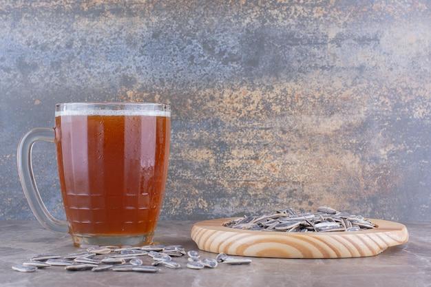 Verre de bière et graines de tournesol sur table en marbre. photo de haute qualité