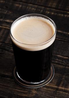 Verre de bière haut avec mousse blanche sur fond de bois
