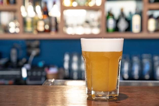 Verre de bière légère dans un pub sombre.