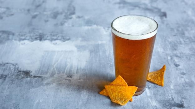 Verre de bière légère sur mur de pierre blanche.