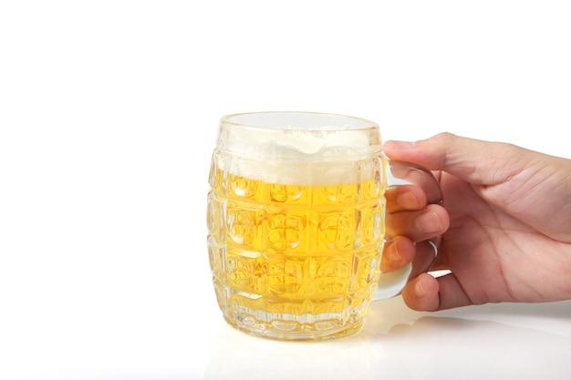 Verre d'une bière à la main isolé sur fond blanc