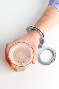 Verre de bière avec des menottes comme symbole de l'abus d'alcool