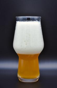 Verre de bière avec mousse isolé sur fond noir