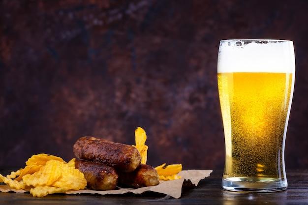 Verre de bière avec mousse, saucisses frites et chips sur fond noir