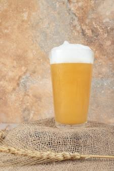 Verre de bière mousseuse sur du blé en toile de jute