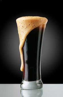 Verre de bière noire avec de la mousse