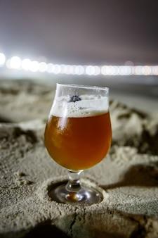 Un verre de bière à la plage de copacabana à rio de janeiro, brésil. éclairage de nuit.