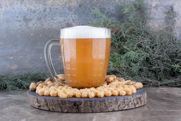 Verre de bière, pois et cacahuètes sur pièce en bois