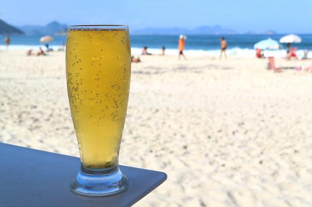 Verre de bière pression froide contre la plage ensoleillée de copacabana à rio de janeiro, brésil, amérique du sud