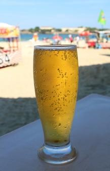 Verre de bière pression froide sur la plage ensoleillée de copacabana à rio de janeiro, brésil