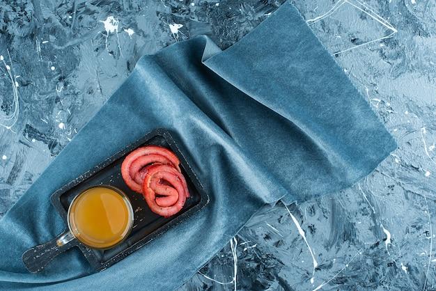 Un verre de bière et de saindoux de porc sur une planche sur un morceau de tissu, sur la table bleue.