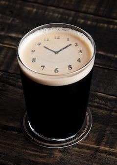 Verre de bière stout top avec forme d'horloge sur fond de bois