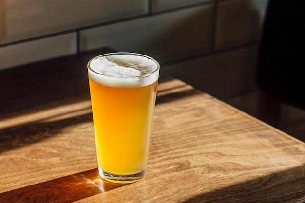 Un verre de bière sur une table en bois.