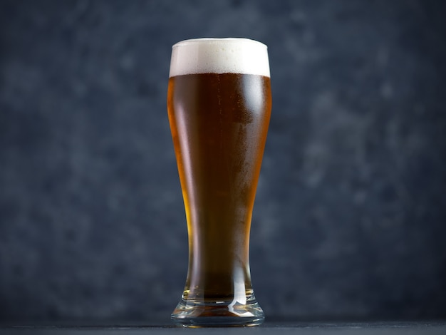Verre à bière sur une table sombre se bouchent