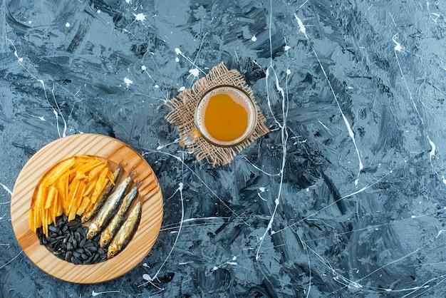 Un verre de bière sur la texture et des apéritifs sur une assiette en bois, sur la table bleue.