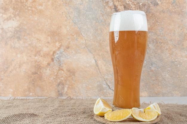 Verre de bière avec des tranches de citron sur de la toile de jute.