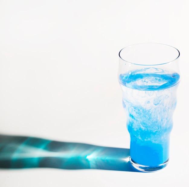 Verre bleu d'eau avec une ombre lumineuse sur fond blanc