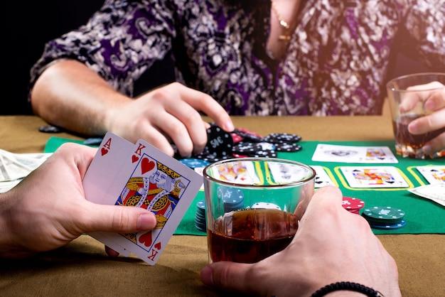 Verre avec une boisson alcoolisée et des cartes dans les mains des hommes