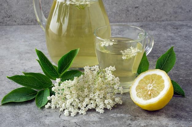 Verre avec boisson aux fleurs de sureau avec tranche de citron.