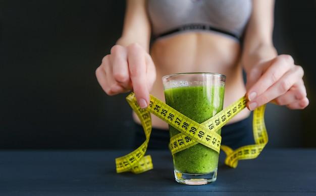 Verre à boisson diététique vert. concept de perte de poids. lumière naturelle, surface sombre.