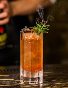 Un verre de boisson froide colorée avec des feuilles de romarin et des glaçons.