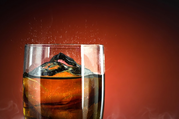 Verre de boisson gazeuse avec des éclaboussures de glace sur fond de fumée fraîche. verre cola avec rafraîchissement estival.