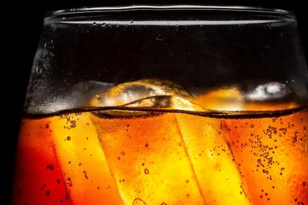 Verre de boisson gazeuse avec éclaboussures de glace sur fond sombre verre de cola à celebrat
