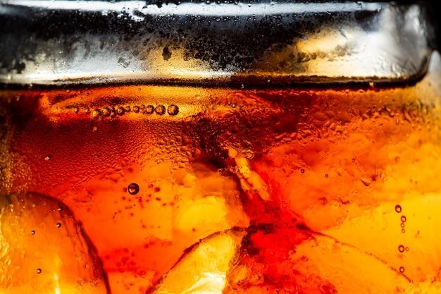Verre de boisson gazeuse avec éclaboussures de glace sur fond sombre verre de cola dans le concept de fête de célébration