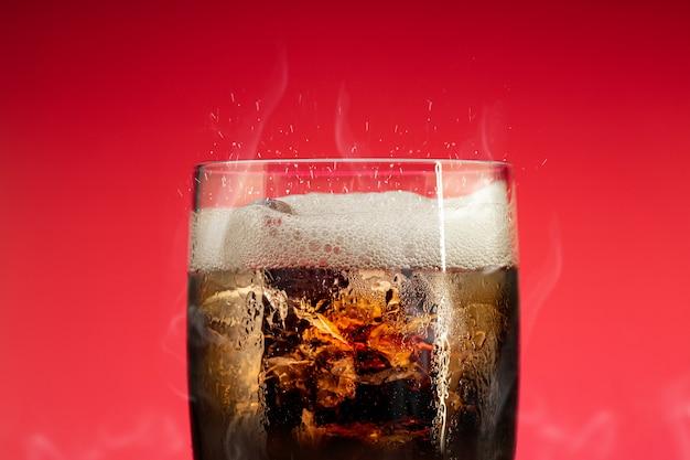 Verre à boisson gazeuse avec éclaboussures de glace. verre cola avec rafraîchissement estival.
